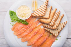 Dinner with sliced salmon. Toast and basil Royalty Free Stock Images