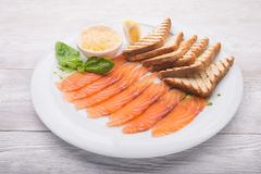 Dinner with sliced salmon. Toast and basil Stock Image