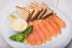 Dinner with sliced salmon. Toast and basil Royalty Free Stock Image