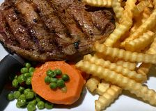 Ribeye steak, crinkle-fries, and peas & carrots royalty free stock photos