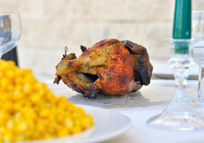 Dinner table with a chicken and corn Royalty Free Stock Photography