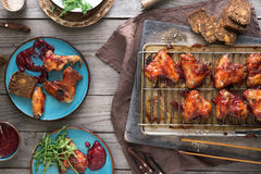 Dinner table with chicken wings in cranberry sauce Royalty Free Stock Image