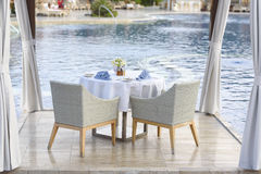 Dinner table for couple with white tablecloth. And blue napkins by the pool. Romantic dinner by the pool. Dining table for couple Stock Images