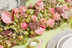 Dinner table flower arrangement. Beautiful twotone flower arrangement in soft pink and green on a christmas dinner table Stock Photography