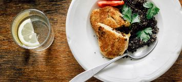 Dinner table Fried prunes oat cutlets black quinoa plate wooden. Dinner table. Fried prunes oat cutlets with black quinoa in plate on wooden table top view royalty free stock photo