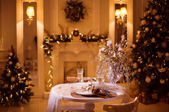 Dinner table in great apartments with decorated Christmas trees Stock Images