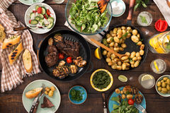 Dinner table with grilled steak, vegetables, potatoes, salad, sn. Dinner table with grilled steak, grilled vegetables, potatoes, salad, different snacks and stock photos