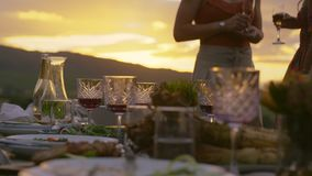Dinner table at party in the yard. Dinner table with food and wine glass, with young people standing in background at party. Dinning table at party in the yard stock footage