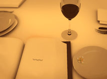 Dinner table with poetry book and wine. Dinner table with wine glass and book stock photo