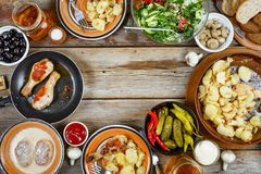 Dinner table with roasted chicken legs with fried potatoes, chimchiuri and chili sauce, grill bean and broccoli as a side dish ove Royalty Free Stock Images