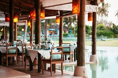 Dinner table and seat by the pool in tropical resort, Phuket Tha royalty free stock images