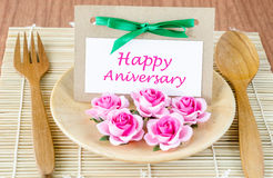 Dinner table setting with Happy Anniversary message card. And pink rose Stock Photo