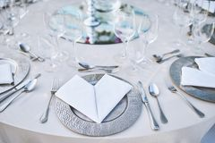 Dinner table setting with stainless plate, fork, spoon and napkin with water glasses in closeup royalty free stock photography