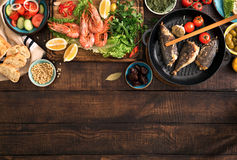 Dinner table with shrimp, fish grilled, salad, snacks with borde Stock Image