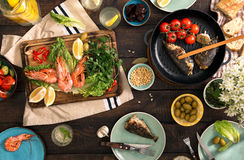 Dinner table with shrimp, fish grilled, salad, snacks and lemona Royalty Free Stock Image