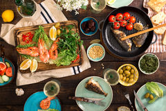 Dinner table with shrimp, fish grilled, salad, snacks and wine. Dinner table with shrimp, fish grilled, salad, different snacks and white wine, top view Royalty Free Stock Photography