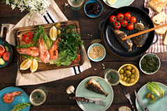 Dinner table with shrimp, fish grilled, salad, snacks and wine Stock Photo
