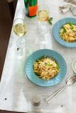 Dinner table Top view two plate pasta carbonara white wine. Dinner table concept. Top view two plate of pasta carbonara with glass of white wine on white wooden Royalty Free Stock Photos