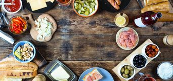 Dinner table. Various snacks and wine. top veiw. Dinner table. Various snacks and wine. Salmon, olives, grilled sausages, buns and other ingredients for hot dogs stock photos