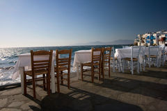 Dinner Tables At Aegean Sea. Dinner Tables with a beautiful view of  Aegean Sea in Mykonos, Greece Royalty Free Stock Images