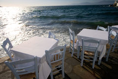 Dinner Tables At Aegean Sea. Dinner Tables with a beautiful view of  Aegean Sea in Mykonos, Greece Royalty Free Stock Photography