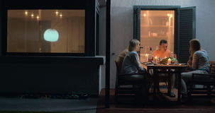 Dinner on the terrace in family circle. Dinner of a big family. Grandparents, parents and child going to meal on outdoor terrace by the house with lit candles on stock video footage