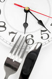 Dinner time. Fork and wall clock with white background, concept of dinner time stock photos