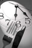 Dinner time. Knife, fork and wall clock, concept of dinner time stock photography