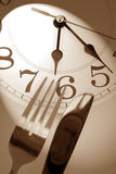 Dinner time. Fork, knife and wall clock, concept of dinner time stock images