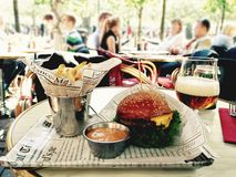 Dinner time. Burger, fries and beer on the table of open terrace cafe Stock Images