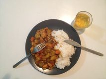 Dinner time. Chinese dinner - curry style chicken with glass of Stock Images