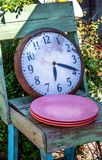Dinner time concept, clock and plates. Concept of dinner time, a clock, chair and a pile of plates, resting in a garden stock photo