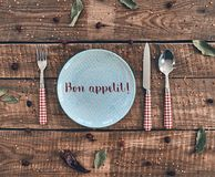 Dinner time. High angle shot of empty plate, fork, spoon, knife lying on rustic table stock images