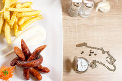 Dinner time. Food on wood table with clock Royalty Free Stock Photos