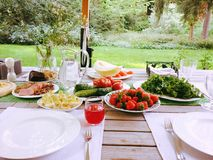 Dinner time. Fruits and vegetables. An appetitive dinner on the open air Royalty Free Stock Photography