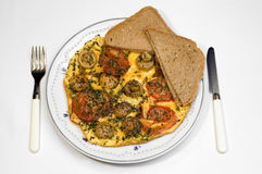 Dinner time, omelet. Dinner time, omelet with tomato, mushroom and chive and fresh baked sunflower seed bread. Photographed over white, isolated Stock Photography
