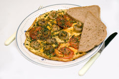 Dinner time, omelet. Dinner time, omelet with tomato, mushroom and chive and fresh baked sunflower seed bread. Photographed over white, isolated Stock Photos