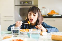 Dinner time with pasta. Cute and happy little girl eating pasta with tomato sauce and powdered cheese in the kitchen at home Stock Photos