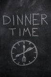 Dinner time text with clock on black chalkboard Royalty Free Stock Images