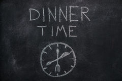 Dinner time text with clock on black chalkboard. Dinner time text with clock drawn with white chalk on blackboard Stock Image