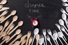 Dinner time written on blackboard with chalk. Dinner time background. Red alarm clock and lots of disposable cutlery on blackboard with inscription written with stock photo