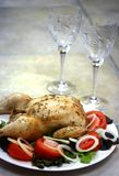 Dinner for two. A plate of roast chicken with fresh salad garnish consisting of fresh tomatoes and onions, with two wine glasses in the background Royalty Free Stock Image