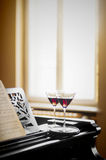 Dinner for two with red wine. Two glasses with red wine on a piano for a romantic date with classical music Stock Photography