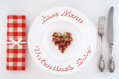 Dinner for two on Valentines Day. Table setting with heart of roses on a plate. Stock Photography
