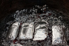 Dinners (close -up). Image of tim foil dinners on the coals Royalty Free Stock Photo