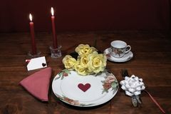 Dinnerware фарфора цветочного узора точный с соответствуя плитой, чашкой и поддонником букет желтых роз, розовая салфетка, silver стоковые фото
