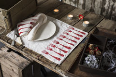 Dinnerware with Matching Napkin and Placemat on Wooden Table. A white dinner napkin with red fork pattern design on white round dinner plate next to pair of Stock Photo