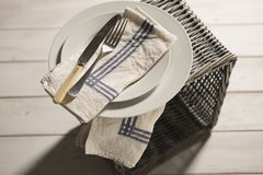 Dinnerware and Napkins on Wicker Box Over Blurred Wooden Backgro Royalty Free Stock Photo