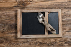 Dinnerware - rozwidlenie i łyżka w pielusze na chalkboard na drewnianym Fotografia Royalty Free