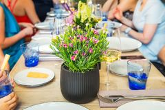 Dinning with family, friends. Blurred no face people enjoying meal while sitting at the dinning table with focus on the flower pot stock photo